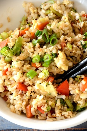 close up of vegetable fried rice with green onions, red pepper.