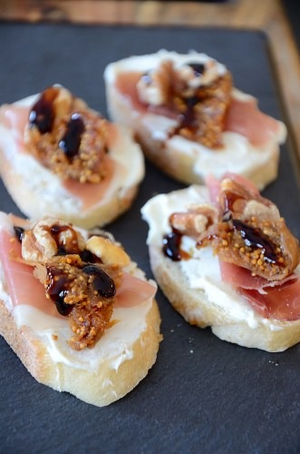 Crostini with cream cheese, serrano ham, fig and walnut on a slate tray