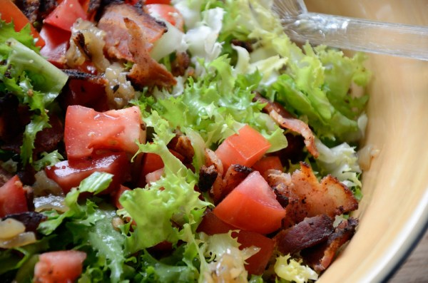 Close up of salad with escarole, bacon and tomato in a bowl