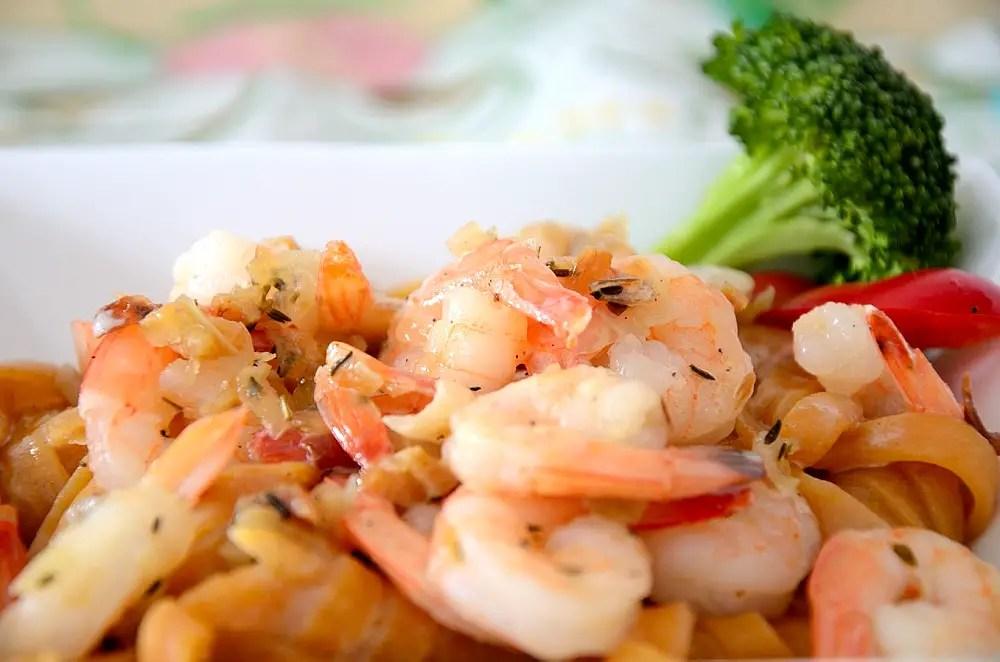 Close up of jumbo shrimp over pasta with a creamy sauce.