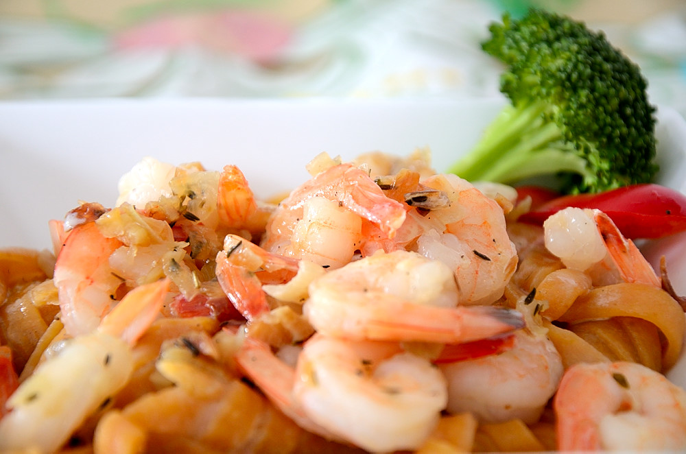 Close up of jumbo shrimp over pasta with a creamy sauce.