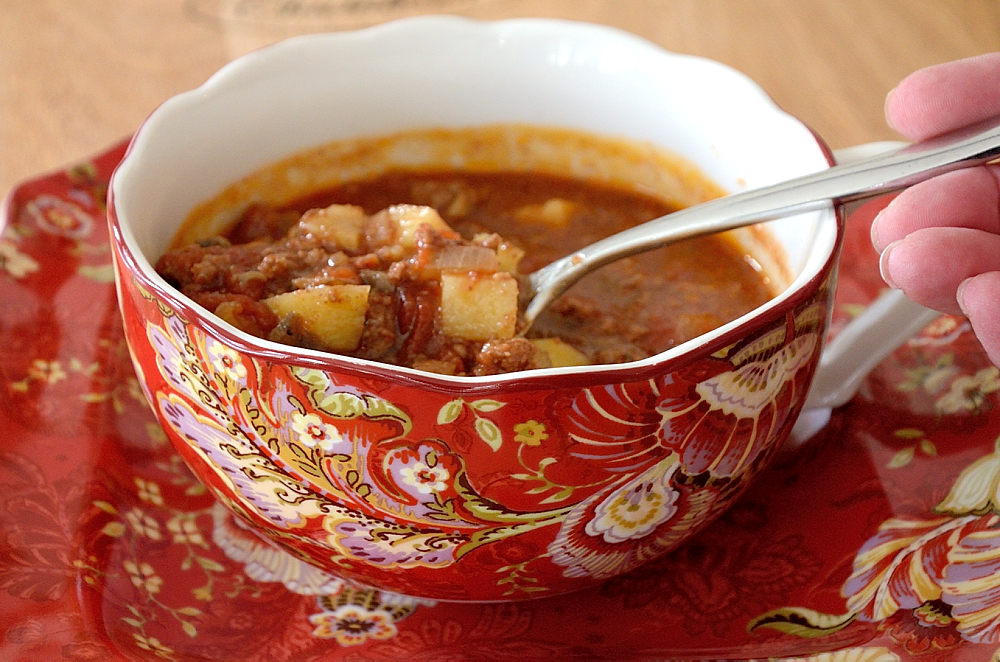 Hamburger soup with a spoon in a soup bowl