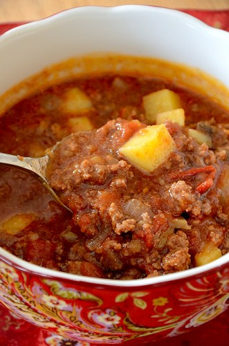 Close up of spoonful of meaty hamburger and potato soup