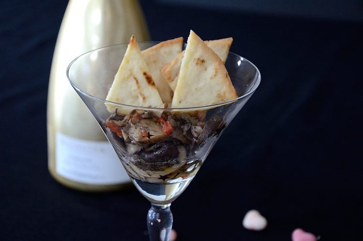 Creamed mushrooms served in a martini glass with pita chips