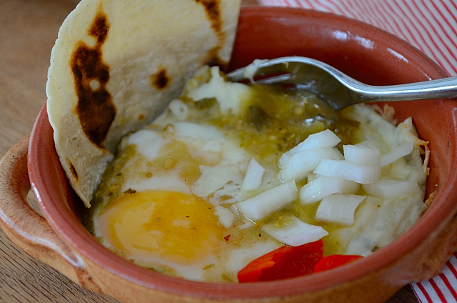 Baked eggs on bed of tortillas with Mexican Green sauce