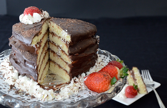 Chocolate layer cake garnished with whipped cream and strawberries