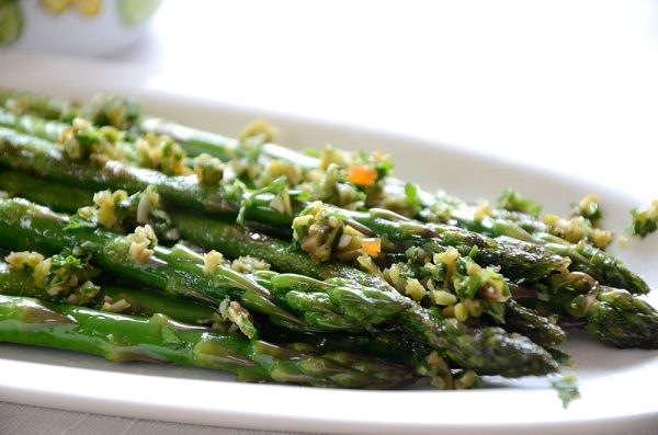 Asparagus spears on serving plate sprinkled with olive gremolata