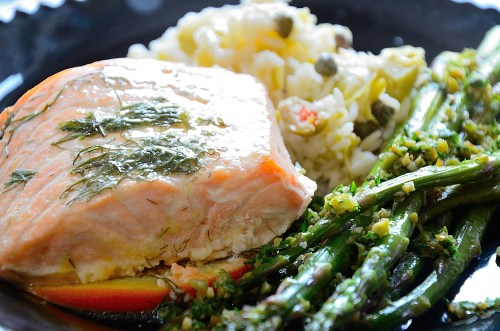Salmon fillet on orange slices with fennel fronds plated with asparagus and rice