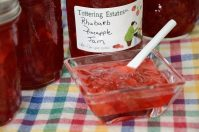 Rhubarb Pineapple Freezer Jam in a small dish with jam jars behind.