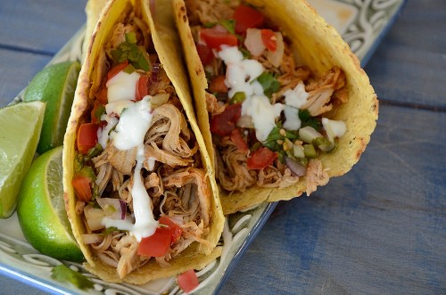 Two tacos filled with pulled pork and garnished with pico de gallo and lime crema