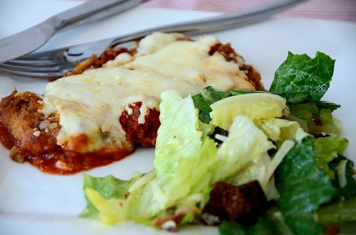 Eggplant Parmigiana scallop beside caesar salad on a plate