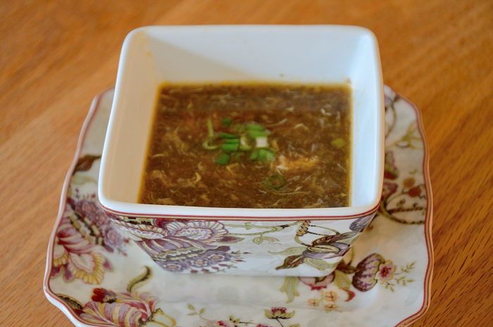 Square soup bowl filled with hot and sour mushroom soup
