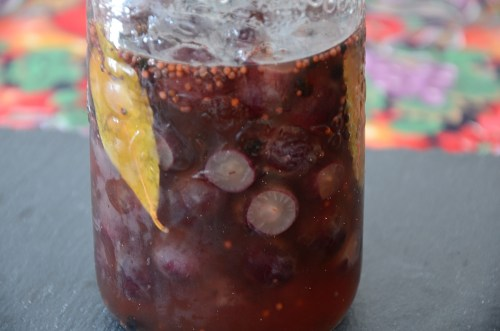 Pickled grapes in brine in a mason jar.