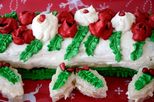 Yule Log Sandwich loaf deorated with roses and leaves and garnished with Holly shaped tea sandwiches