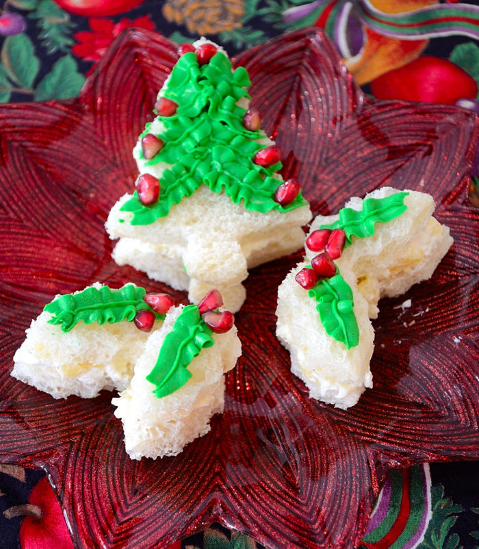 Christmas tree shaped sandwich with green cream cheese icing and pomegranate decorations