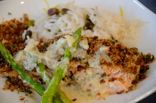 A plate with Herb crusted salmon beside Lemon Pistachio rice sauced with Lemon Cream