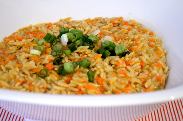 bowl of carrot orzo with green onion garnish