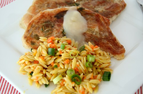 2 chicken cutlets with crispy sage and prosciutto on a plate with carrot orzo