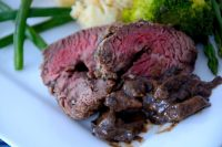Slice of rare Chateaubriand on a plate with mushroom sauce