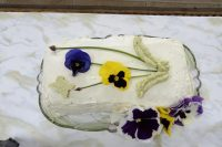 Chicken Avocado Sandwich cake decorated with purple and yellow pansies, chives for stems and piped avocado mousse for leaves