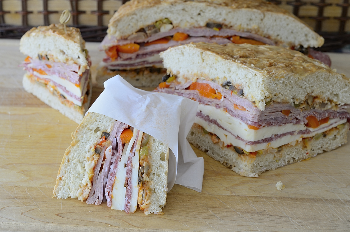 wedges of muffuletta sandwich filled with olive relish, cold meat and cheese slices