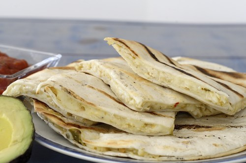 Quartered quesadillas on a plate with avocado on the side