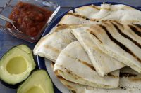 Plate of grilled chicken quesadillas with avocado and salsa