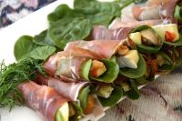 Cheese matchsticks with spinach leaves wrapped into a spiral with a prosciutto slice, on a platter