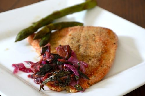 Panfried trout with cornmeal crust and blood orange relish on a plate