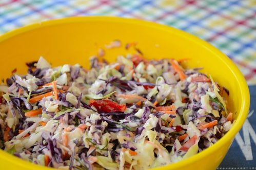 Bright yellow bowl filled with coleslaw made from red and green cabbage with red pepper
