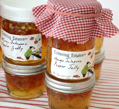 Half pint jars of Mango Jalapeno Pepper Jelly with checkered red cloth on cap.