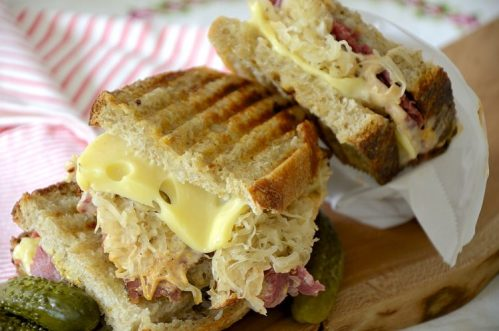 Two halves of a Reuben Sandwich on a board with Swiss Cheese and Sauerkraut oozing out of the sandwich