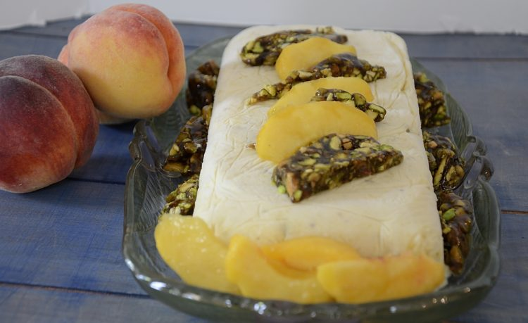 Semifreddo on a plate garnished with fresh peaches and pistachio brittle.