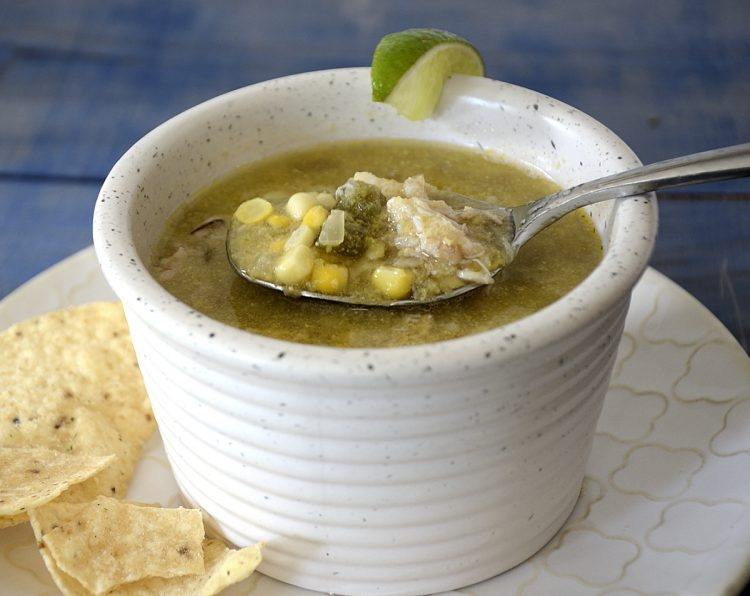 Bowl of sweet corn soup with tortilla and lime garnish