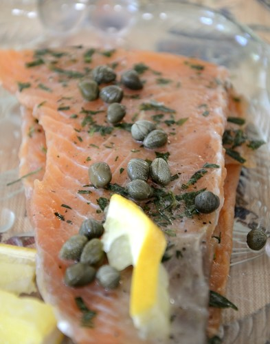 fillet of cured salmon with capers and twist of lemon.