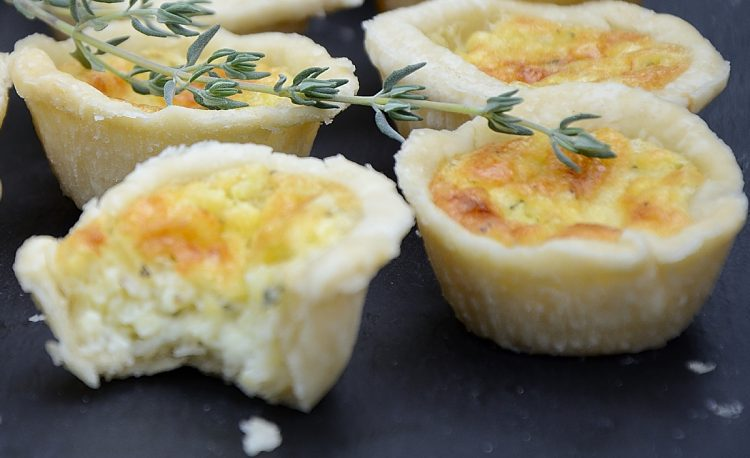Mini tarts with cheesy quiche-like center on a serving board with a sprig of thyme garnish.