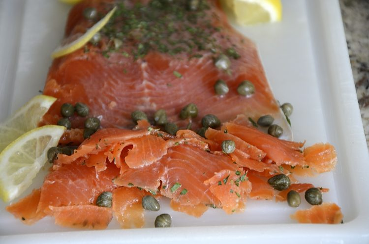 Fillet of Gin cured trout thinly sliced with capers and lemon on a cutting board.
