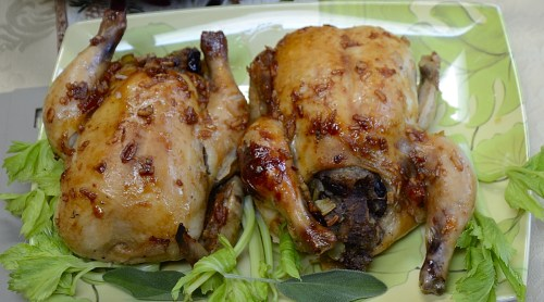 Two stuffed Cornish hens on a platter with celery leaves and sage garnish.