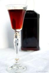 Liqueur glass of keto chocolate liqueur with liqueur bottle in background.
