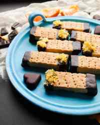 Plate of rectangular Scottish shortbread biscuits dipped in chocolate with oranze zest.