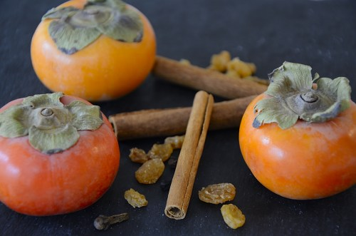 Three persimmons on a tray with golden raisings and cinnamon sticks.
