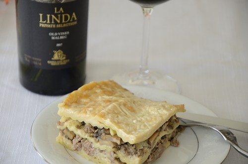Plate with a square of creamy beef, mushroom lasagne with a bottle of Malbec and a glass of red wine on the side.