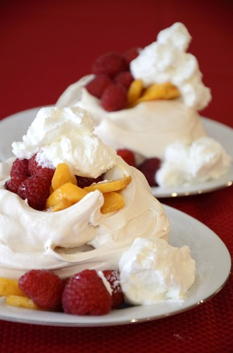Two pavlovas on dessert plates topped with fresh persimmon slices, raspberries and whipped cream.