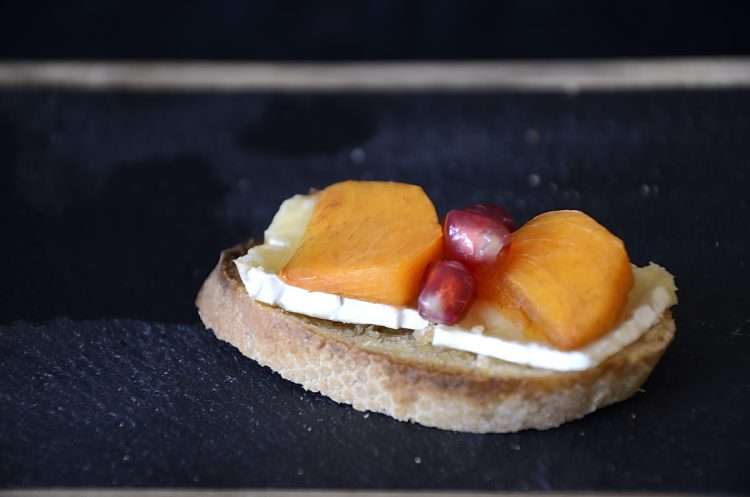 Persimmon slices and pomegranate seeds on melted Brie on baguette slice.