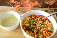 Colourful salad bowl of yellow corn, orange and red peppers and grilled green onions.