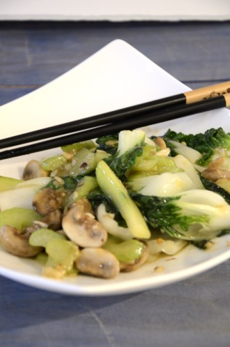 Stir fried Chinese Bok Choy with mushrooms, celery and cucumber plated with chop sticks.