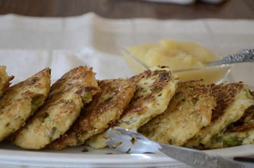 Fried sauerkraut cakes stacked on a serving plate with apple sauce in the background.