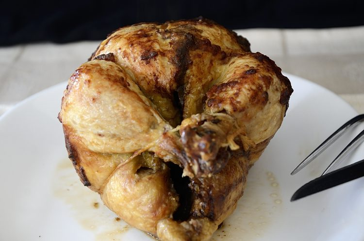 Golden brown rotisserie chicken with parmesan crust.
