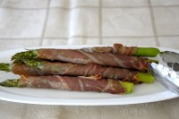 Spears of asparagus wrapped in prosciutto in a dish fresh from the air fryer.