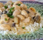 Close up of French rabbit in mustard sauce with pearl onions and mushrooms on a bed of rice.